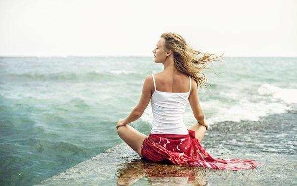 женщина медитирует у моря