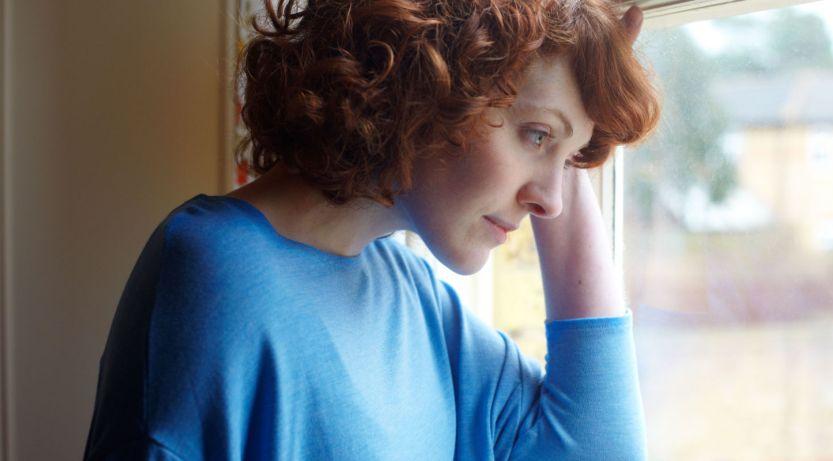 женщина в печали стоит у окна