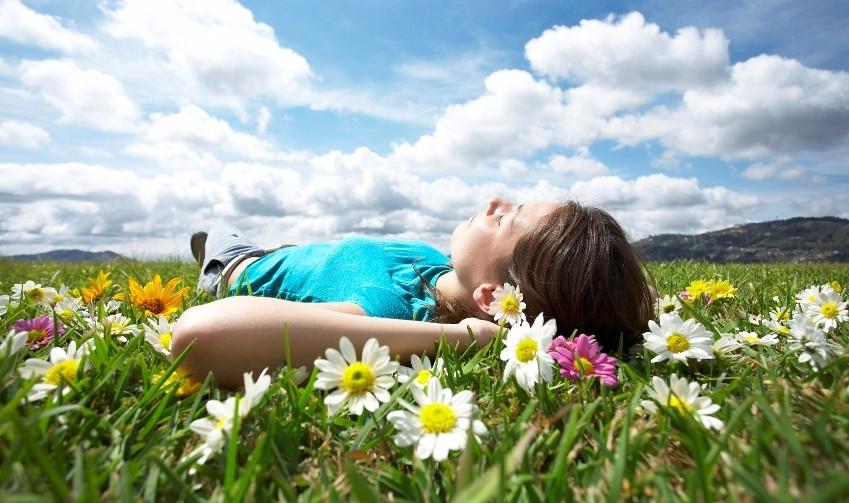 девушка лежит в поле ромашек