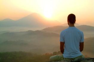 человек медитирует на горе