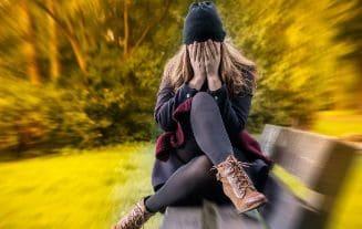девушка сидит на скомейке в депресии