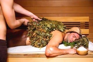 мужчина парится в бане с веником