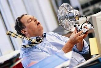 мужчине плохо в жару, обдувается вентелятором