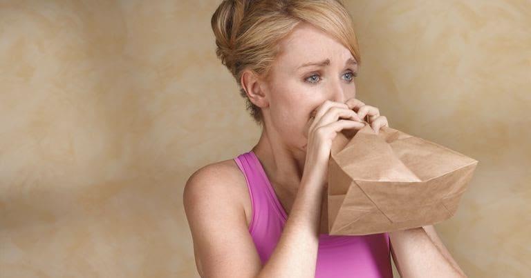 девушка дышит в пакет в приступе паники