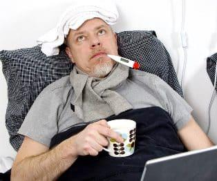мужчина болеет, лежит в постели с лекарствами