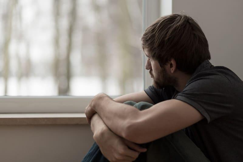 грустный мужчина сидит у окна
