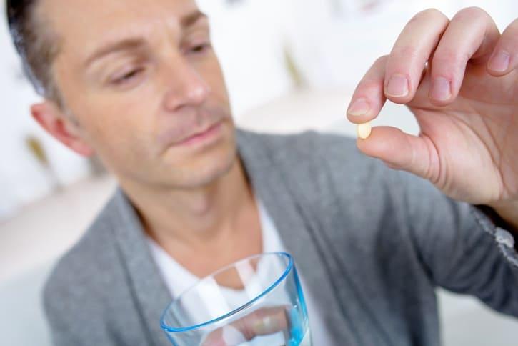 мужчина держит в руке таблетку
