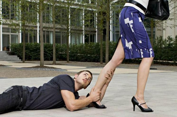 парень цепляется за ногу женщины