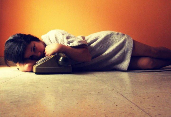 девушка лежит возле телефона