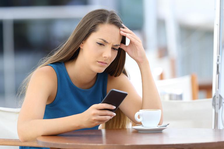 девушка сидит в кафе с телефоном одна
