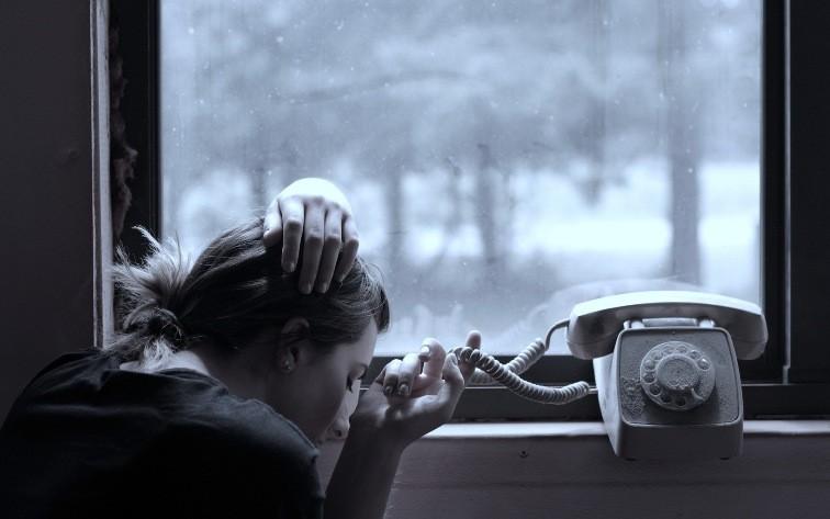 девушка у окна с телефоном