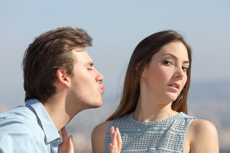 парень пытается поцеловать девушку