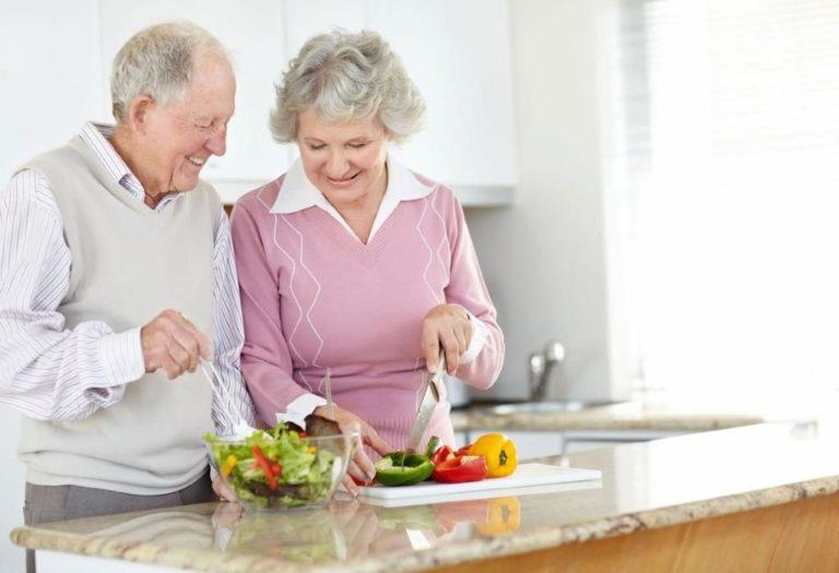 пара пожилая готовит еду