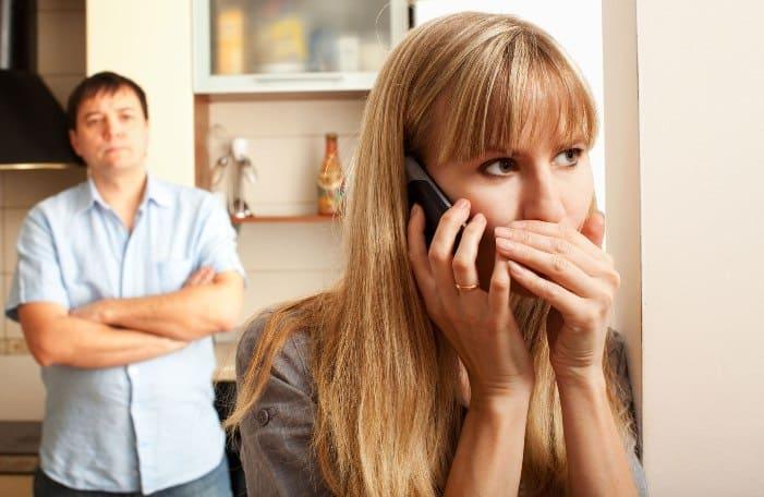 женщина разговаривает по телефону закрывая рот рукой