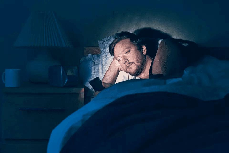 Мужчина в кровати ночью со смартфоном